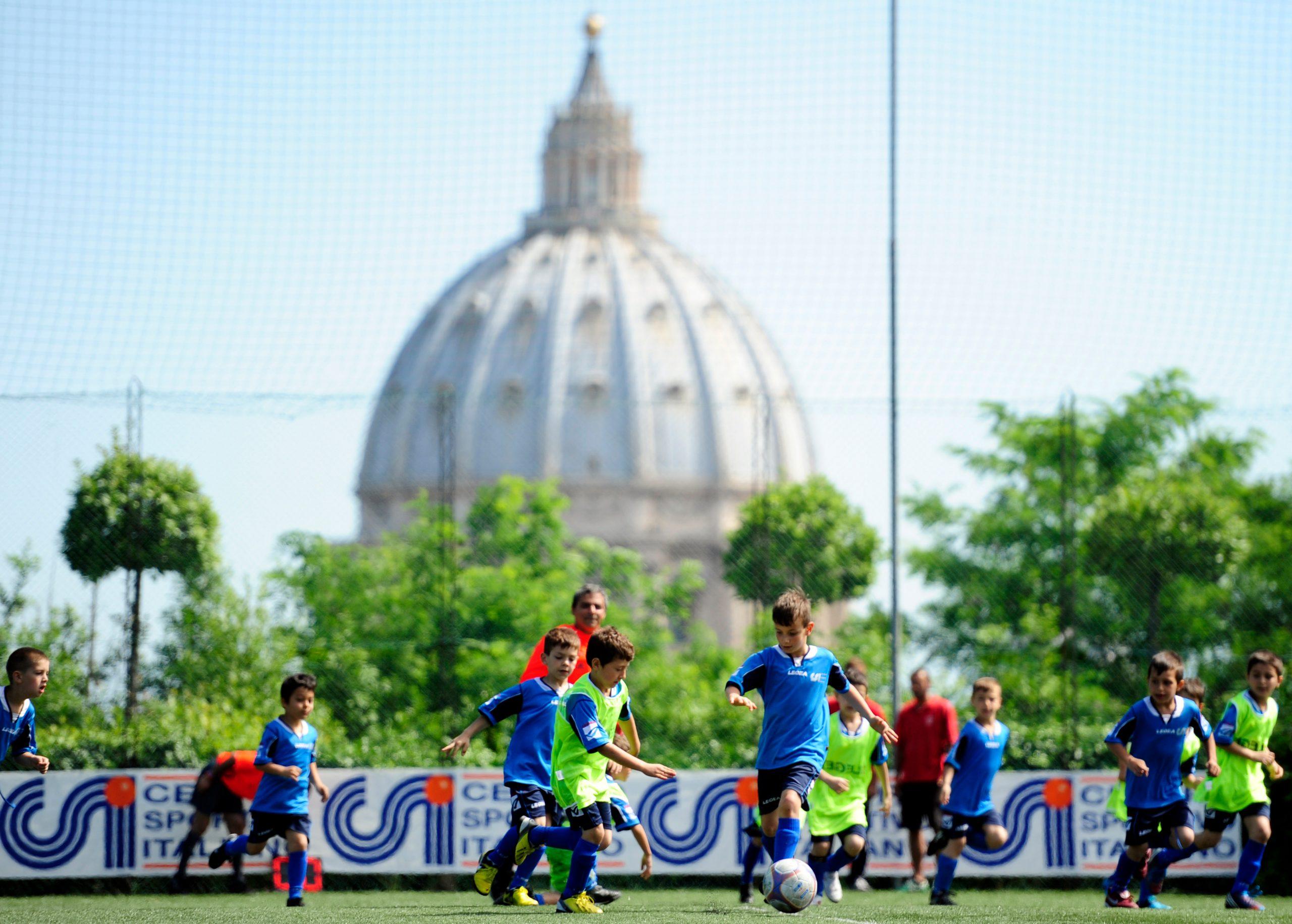 Bambini che giocano a calcio dietro piazza San Pietro