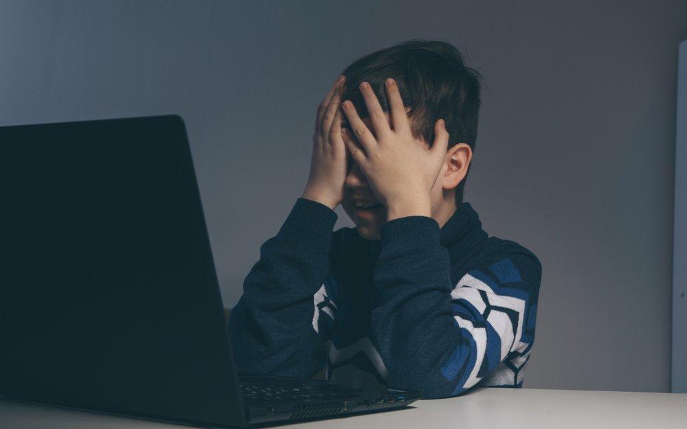 Bambino davanti al PC si copre il volto